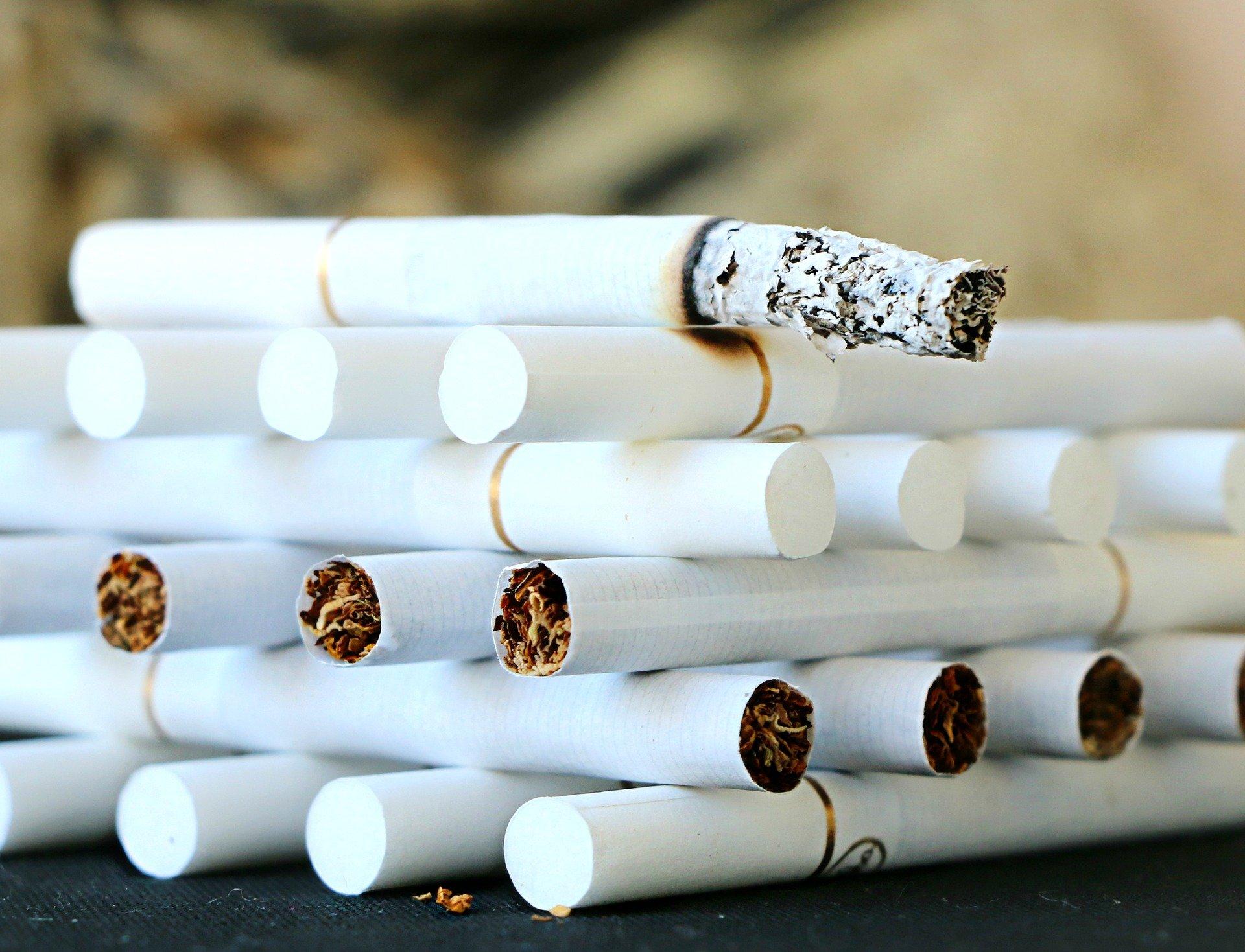 Tas de cigarettes, une cigarette est en train de se consumer.